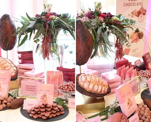 Heilemann Ruby Chocolate arrangiert auf einem Produkttisch mit Dekoelementen